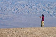 一个年轻人在有智能手机的沙漠拍照片 免版税库存照片