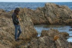 一个年轻人在海洋岩石站立在海旁边 库存图片