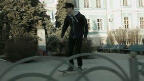 一个年轻人在他的在城市街道上的滑板乘坐 股票录像