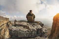 一个年轻人坐峭壁围拢的岩石,在云彩上一个巨大地点,位于云彩背景  库存照片
