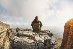 一个年轻人坐峭壁围拢的岩石,在云彩上一个巨大地点,位于云彩背景  免版税图库摄影