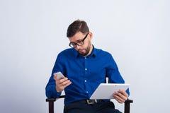 一个年轻人坐并且调查电话 免版税库存照片