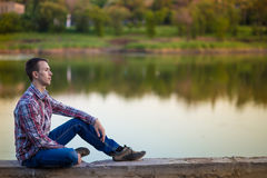 一个年轻人坐河岸 库存图片