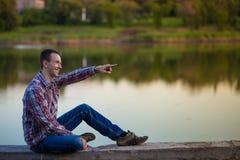 一个年轻人坐河岸 图库摄影