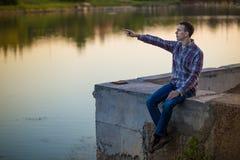 一个年轻人坐河岸 免版税库存照片