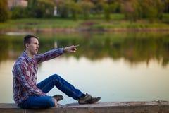 一个年轻人坐河岸 免版税库存图片