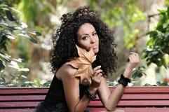年轻黑人妇女在有一片干燥叶子的公园 免版税库存照片