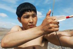 一个年轻人射击一把弓 库存照片