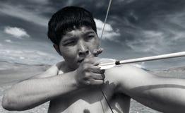 一个年轻人射击一把弓 图库摄影