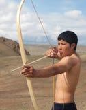 一个年轻人射击一把弓 库存图片