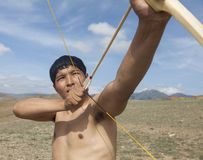 一个年轻人射击一把弓 免版税图库摄影