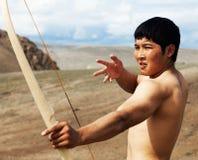一个年轻人射击一把弓 免版税库存图片