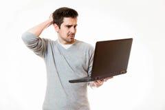 一个年轻人接触他的研究他的膝上型计算机的顶头诡计 图库摄影