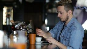 一个年轻人用片剂和饮料咖啡,当坐在酒吧时 股票录像