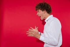 一个年轻人的侧视图白色衬衣叫喊的 免版税库存照片