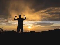 一个年轻人的剪影举起了在双方expresse的一个拳头 库存图片