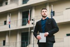 一个年轻人的室外画象有一台片剂个人计算机的在以大厦为背景的手上 到达天空的企业概念金黄回归键所有权 免版税图库摄影