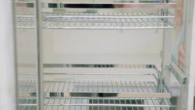 一个年轻人的手在现代陈列室里打开在厨房的一个家具冷冻机门 股票录像