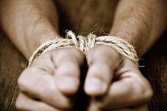 一个年轻人的手栓与绳索 免版税库存照片