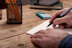 一个年轻人的特写镜头在笔记本写 图库摄影
