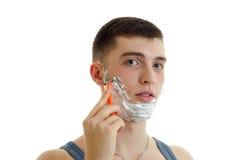 一个年轻人的水平的画象有泡沫的在严重刮他的胡子机器的他的面孔 库存图片