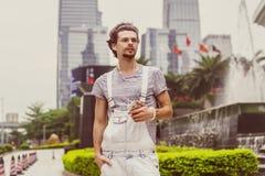 一个年轻人的画象便装样式的与摩天大楼在背景中与电话在手中 免版税库存照片