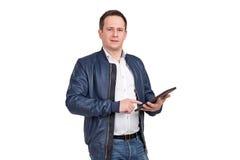 一个年轻人的画象拿着数字式片剂和看在白色背景的蓝色皮夹克的照相机 免版税库存照片