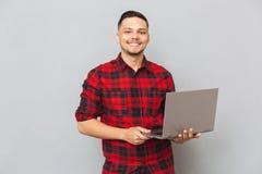 一个年轻人的画象拿着膝上型计算机的格子花呢上衣的 免版税库存图片