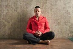 一个年轻人的画象,红色衬衣和黑松驰的,莲花姿势 免版税图库摄影