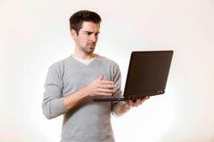 一个年轻人看起来怀疑在他的膝上型计算机 免版税库存图片