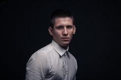 一个年轻人,斜向一边的顶头面孔特写,黑背景 免版税库存照片