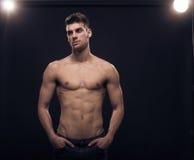 一个年轻人,看斜向一边,反射器赤裸上身的身体 免版税库存图片