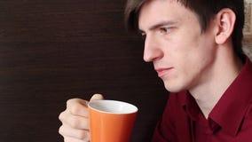 一个年轻人给他的嘴带来橙色杯子并且做一个小饮者 股票视频