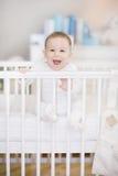 一个轻便小床在家-婴孩的笑的婴孩在床上 免版税库存照片