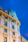 一个巴洛克式的大厦的高峰照亮与在蓝色夜空的黄灯 库存图片