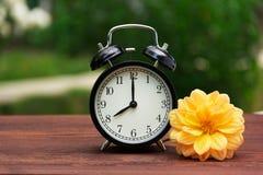 一个经典黑闹钟在桌上的庭院里 在绿色自然本底的一个时钟 复制空间 图库摄影