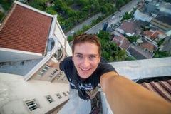 一个年轻勇敢的人,做selfie在摩天大楼的屋顶边缘 苏拉巴亚,印度尼西亚 免版税库存图片