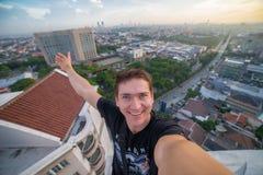 一个年轻勇敢的人,做selfie在摩天大楼的屋顶边缘 苏拉巴亚,印度尼西亚 库存照片