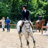 一个年轻十几岁的女孩骑在Germantown慈善马展示的一匹马 免版税库存照片