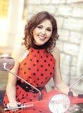 一个年轻可爱的女孩和一辆老滑行车的葡萄酒图象 库存照片