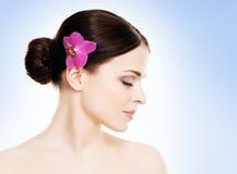 一个年轻和健康女孩的美丽的面孔有一朵兰花花的在她的头发 库存图片