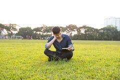 一个年轻和新鲜的亚裔男孩的画象在校园里 免版税库存照片