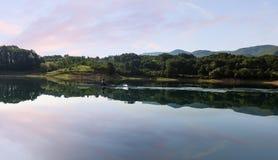 一个年轻唯一短桨划船竞争者在平静的湖用浆划 免版税库存图片