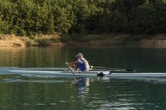 一个年轻唯一短桨划船竞争者在平静的湖用浆划 库存图片