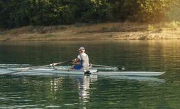 一个年轻唯一短桨划船竞争者在平静的湖用浆划 免版税库存照片