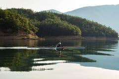 一个年轻唯一短桨划船竞争者在平静的湖用浆划 免版税图库摄影