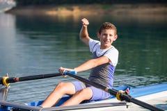 一个年轻唯一短桨划船竞争者在平静的湖用浆划 库存照片