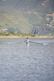 一个年轻唯一短桨划船竞争者在平静的湖用浆划 图库摄影