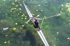 一个年轻唯一短桨划船竞争者在平静的l用浆划 库存照片
