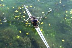 一个年轻唯一短桨划船竞争者在平静的l用浆划 库存图片